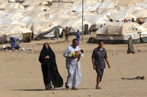 A woman and two men, one of whom is holding an infant, walk on a dry dusty road. Hundreds of refugee tents are behind them.