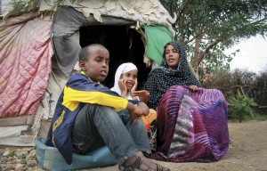 Ubah Mohammed Abdule, right, the mother of the 15 year old Somali boy who stowed away on a flight from California to Hawaii, is interviewed at a refugee camp in Ethiopia. She is sitting in front of a tent and two children are next to her.