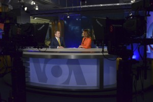 Two anchors sit at a VOA news desk.